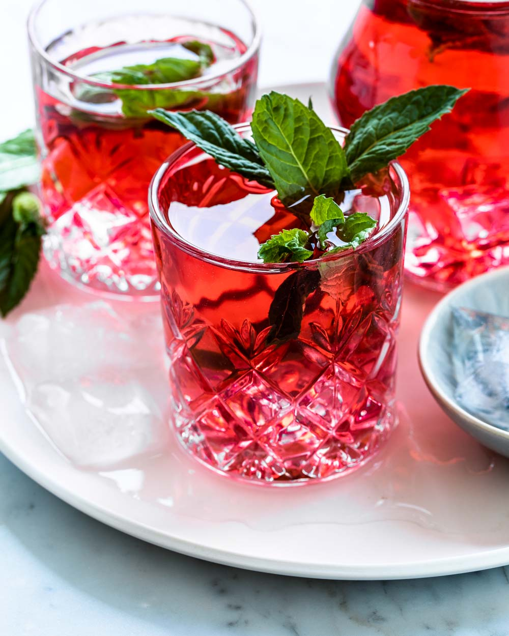 red cold hibiscus tea in glass with fresh mint leaves on white plate in front of a glass and a carafe with hibiscus tea