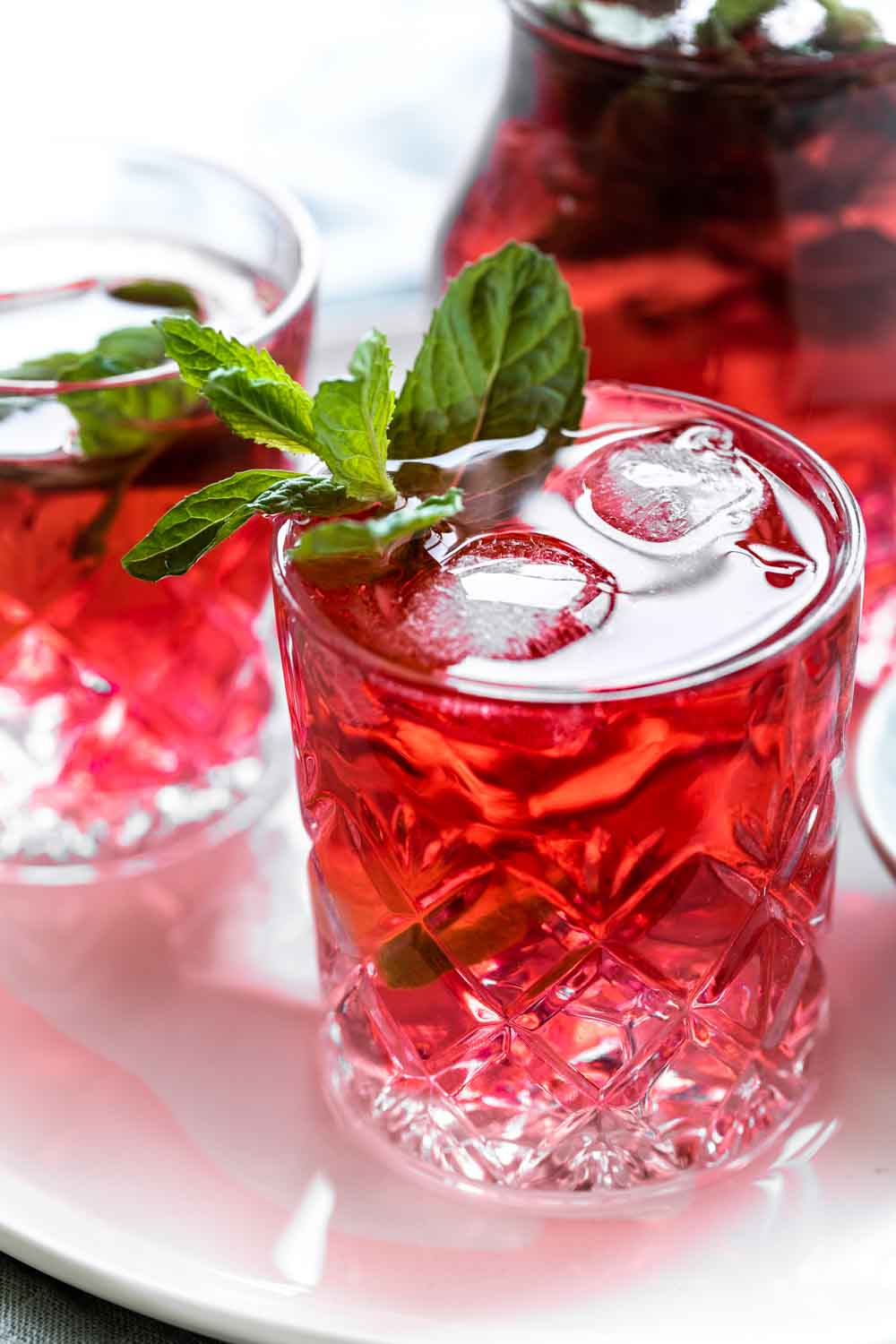 red cold hibiscus tea in glass with fresh mint leaves on white plate