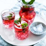 two glasses red cold hibiscus tea with fresh mint leaves next to a small bowl with ice cubes and a small carafe with hibiscus tea and mint leaves on white plate