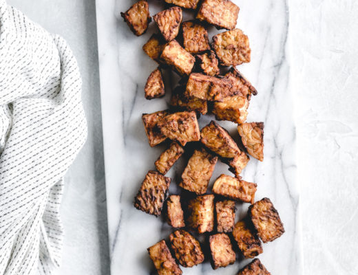 easy baked tempeh on a marble white backdrop next to a napkin