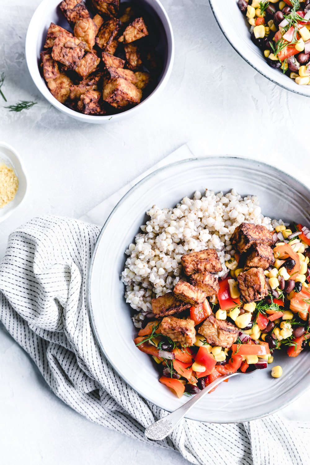 easy baked tempeh in a blue bowl with buckwheat and a salad on a napkin and a white backdrop