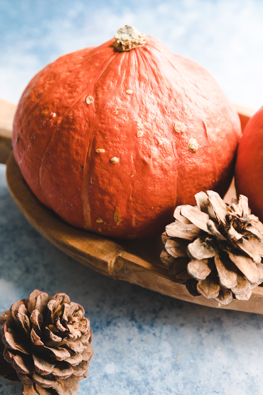 Two pumpkins in a wooden bowl on a blue backdrop next to two pine apples