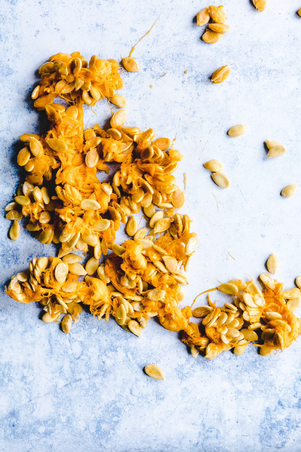 Pumpkin seeds and strings on a blue backdrop