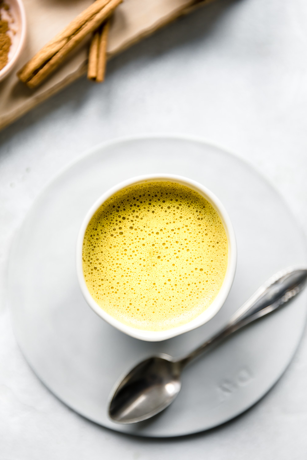 golden milk in white cup on a small white plate next to a silver teaspoon