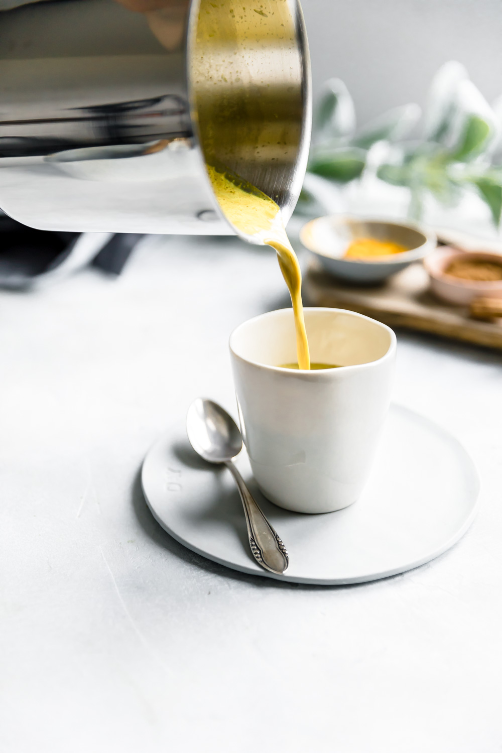 pour shot of golden milk from a stainless steel pot into a white cup on a small white plate next to a teaspoon