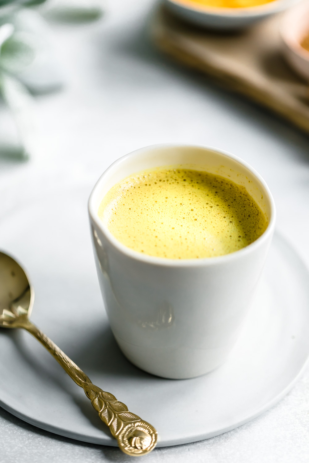 golden milk in white cup on a small white plate next to a golden teaspoon