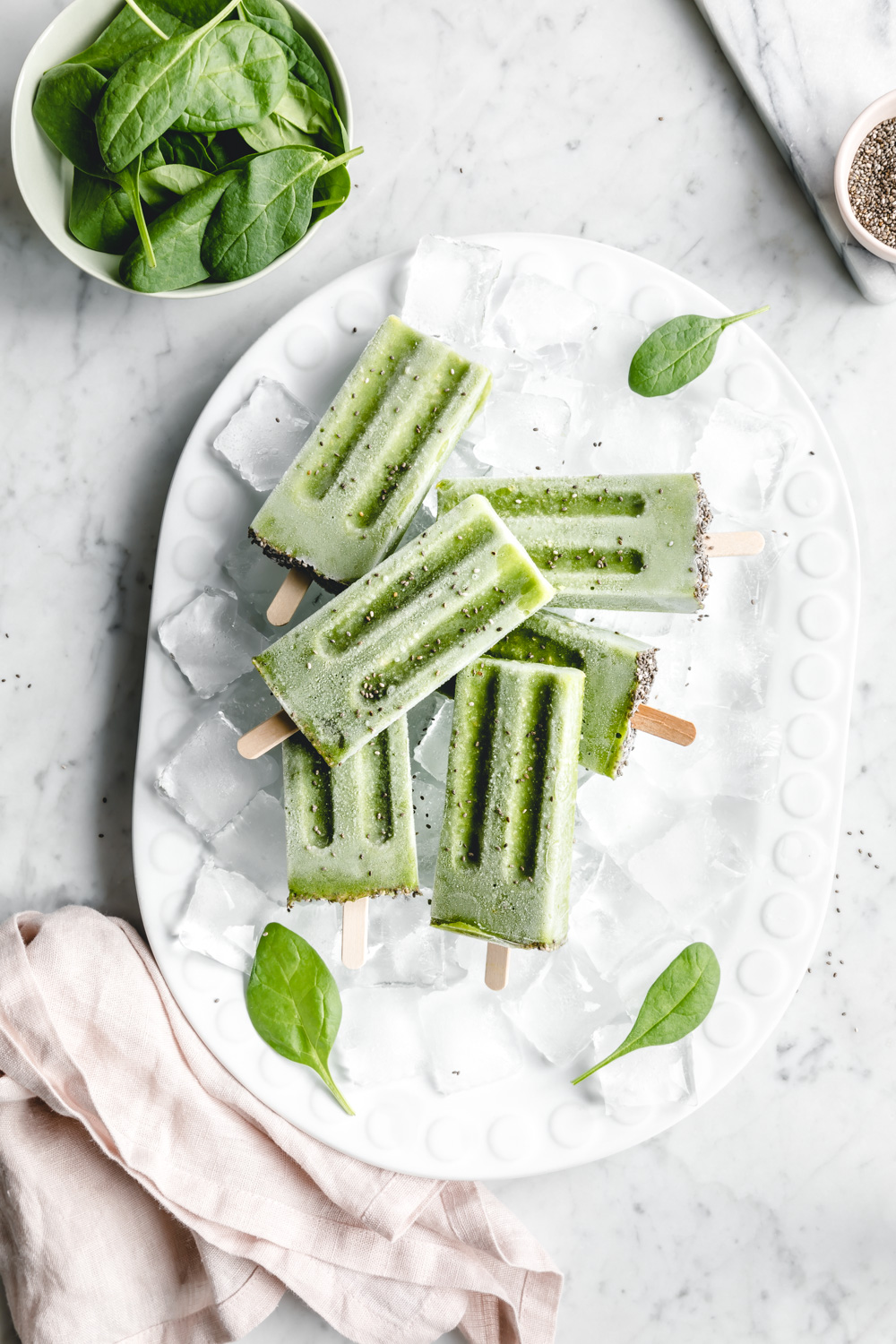 green popsicles on white plate with green leaves