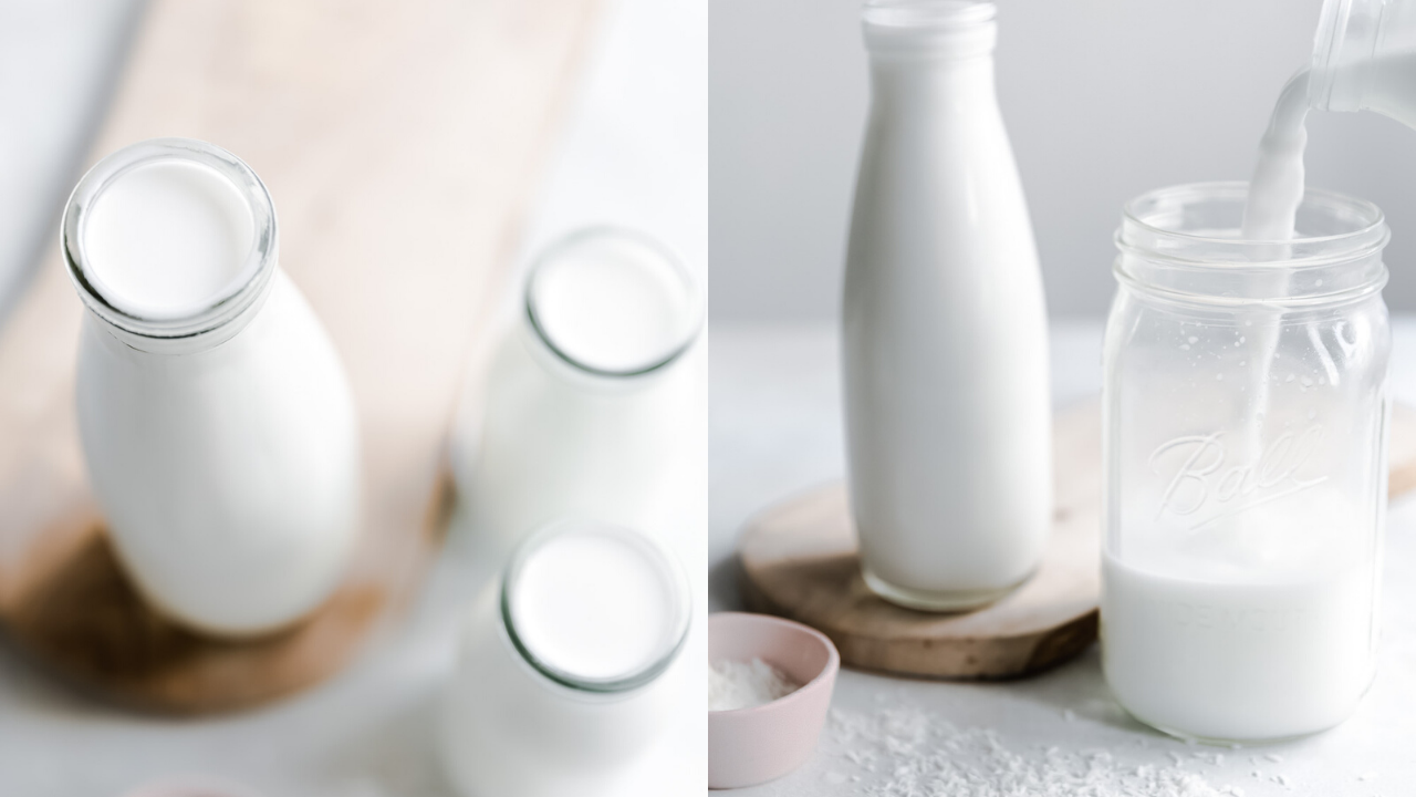 three different size glass bottles with coconut milk with white background and wooden cutting board