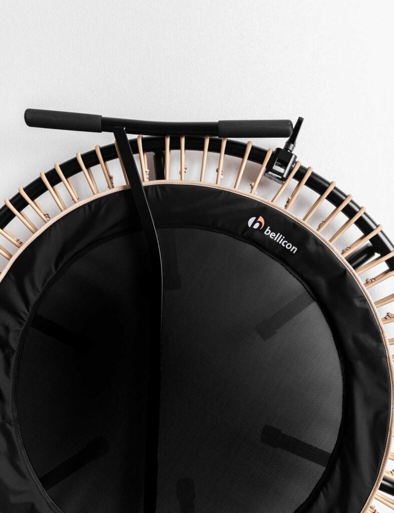 black bellicon rebounder with beige bungees and the stability bar leaning against it