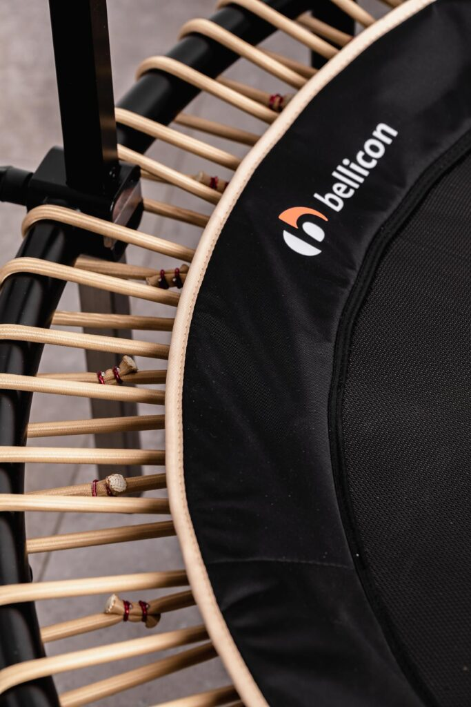 black bellicon rebounder with beige bungees and closeup of the edge of the comfort mat