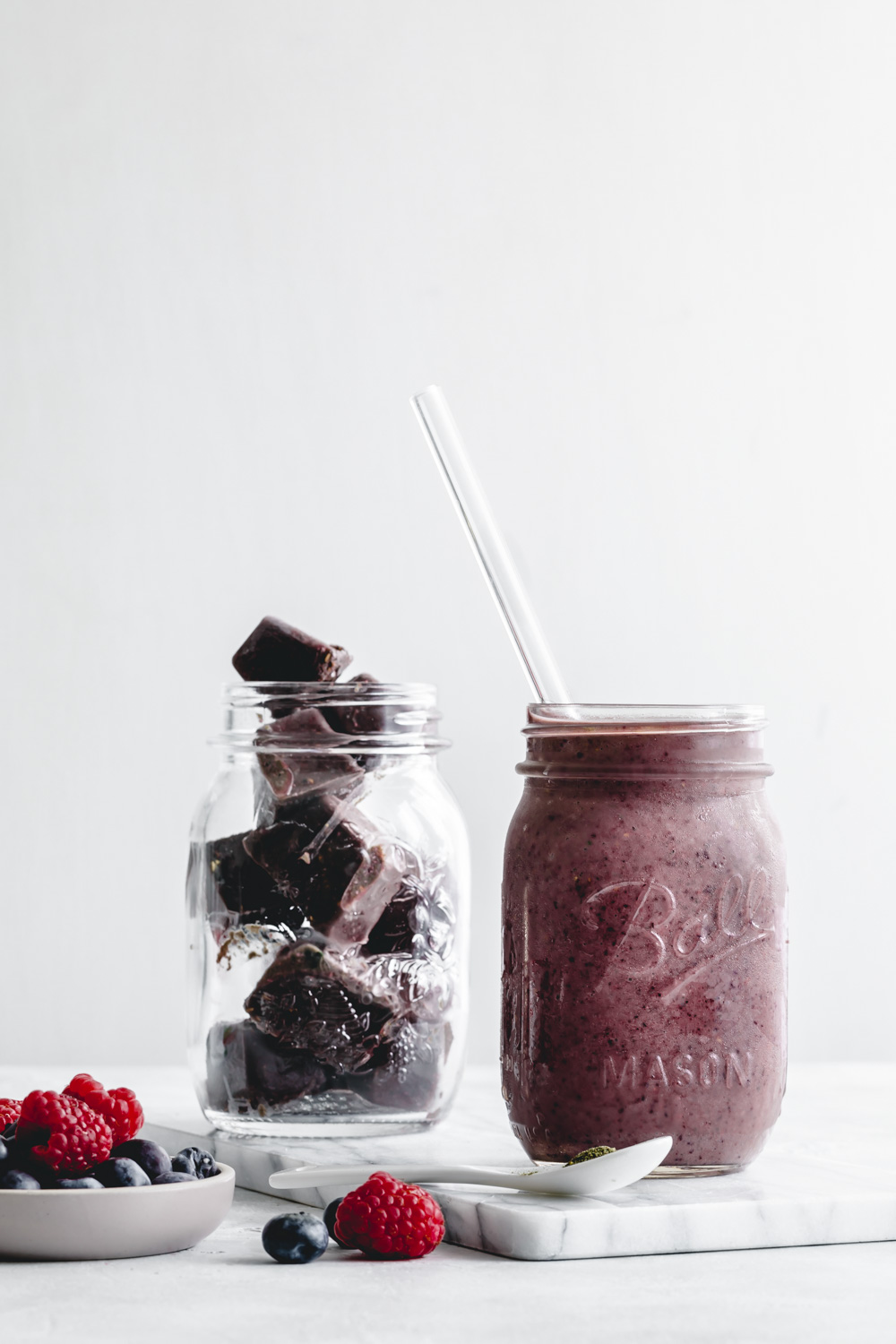 Frozen smoothie cubes in a glass next to a smoothie with a straw