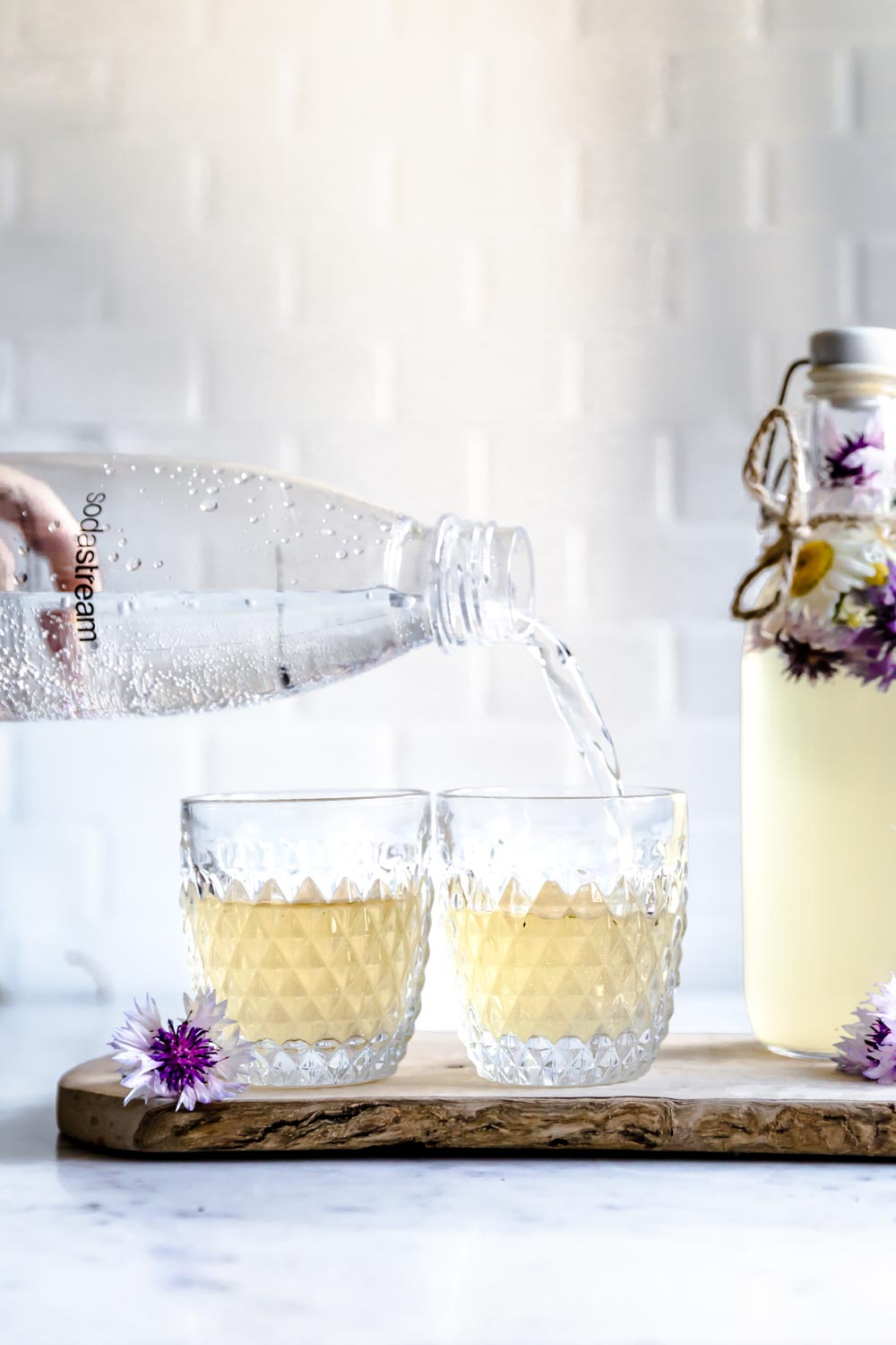 sodastream bottle pouring water in a small glass with tea next to another small glass with flowers and a tall bottle with tea and flowers on a wooden cutting board