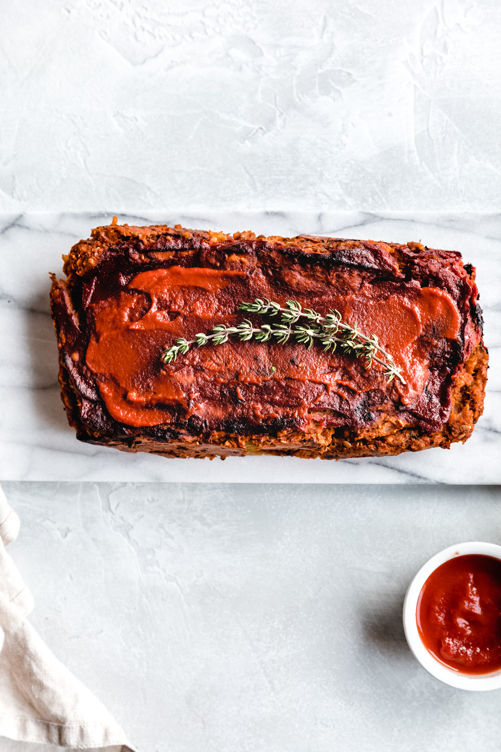 vegan lentil loaf on a marble white cutting board with rosemary on top and a small bowl with ketchup